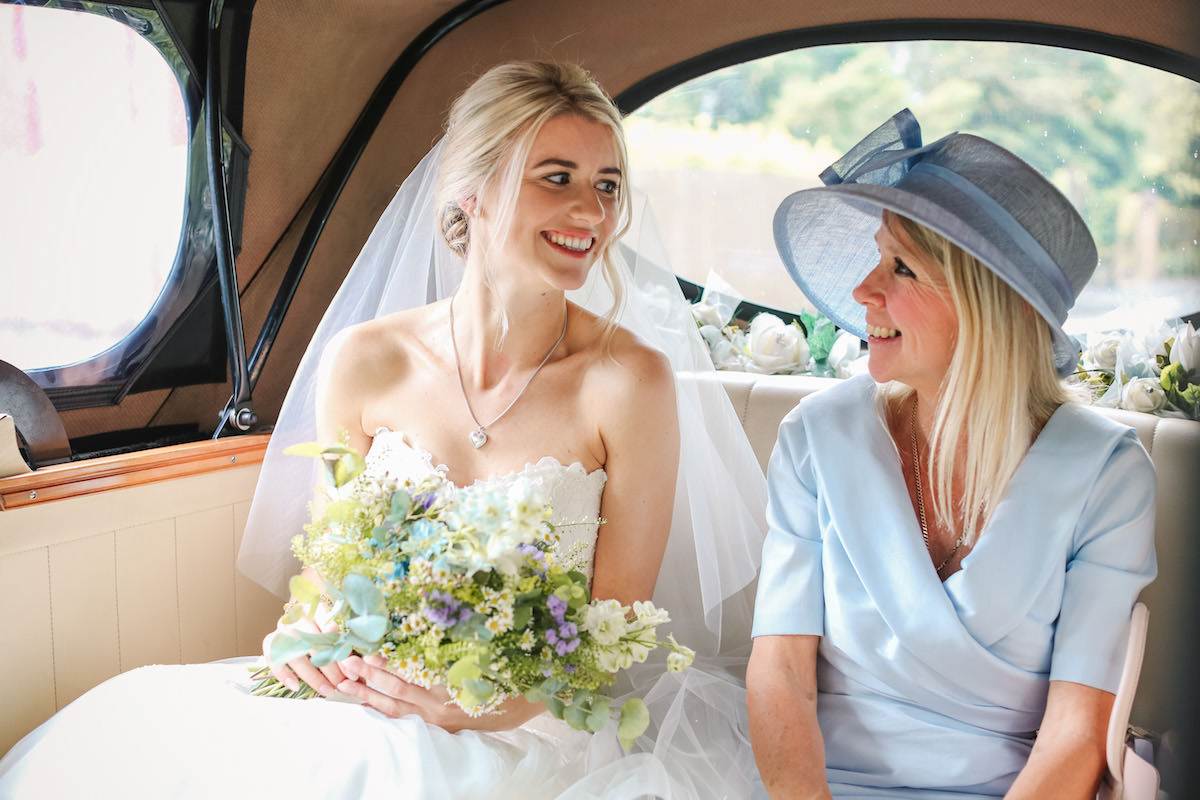 bride in wedding car with mother of the bride